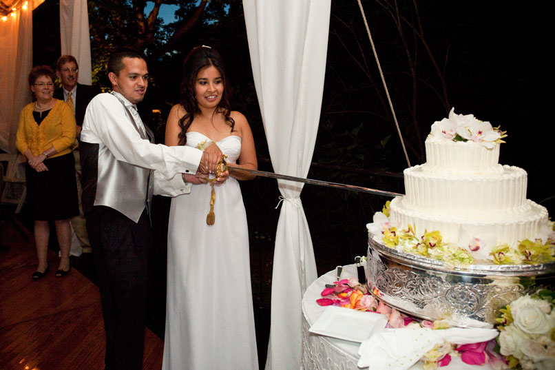 Bride and Groom Cutting The Cake With A Sword