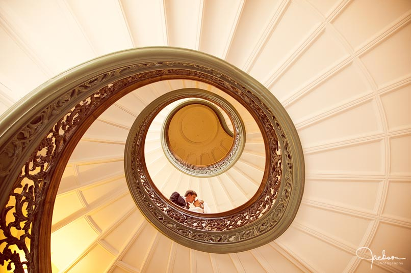 bride and groom on peabody's spiral staircase
