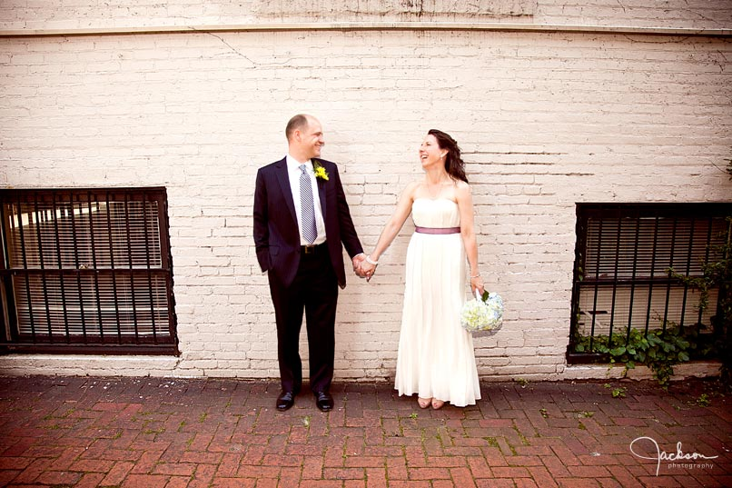 bride and groom posing along Chase Court's wall