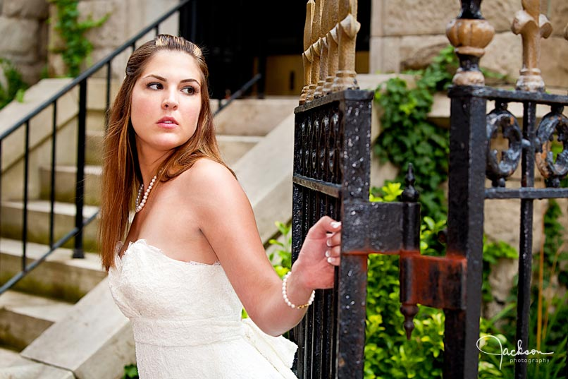 bride posing by iron gate