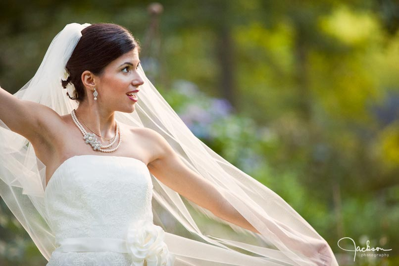 bride stretching veil in the wind