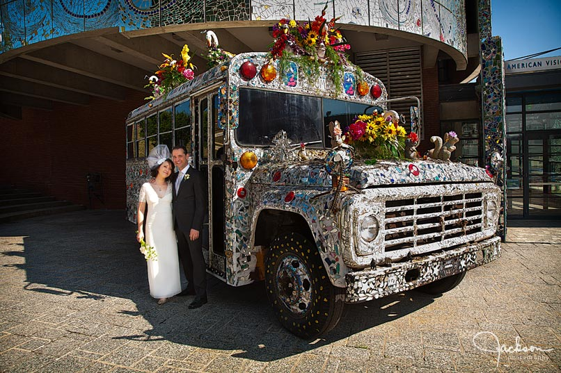 bride and groom in front of visionary decorated bus