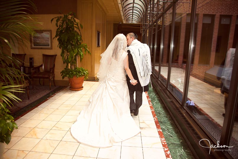 Bride and groom walking down windowed hallway