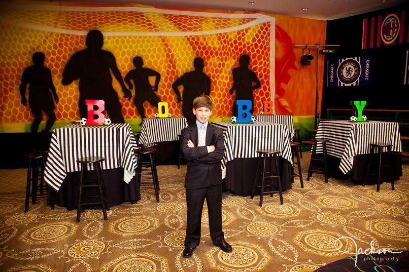 bar mitzvah boy in front of lettered tables
