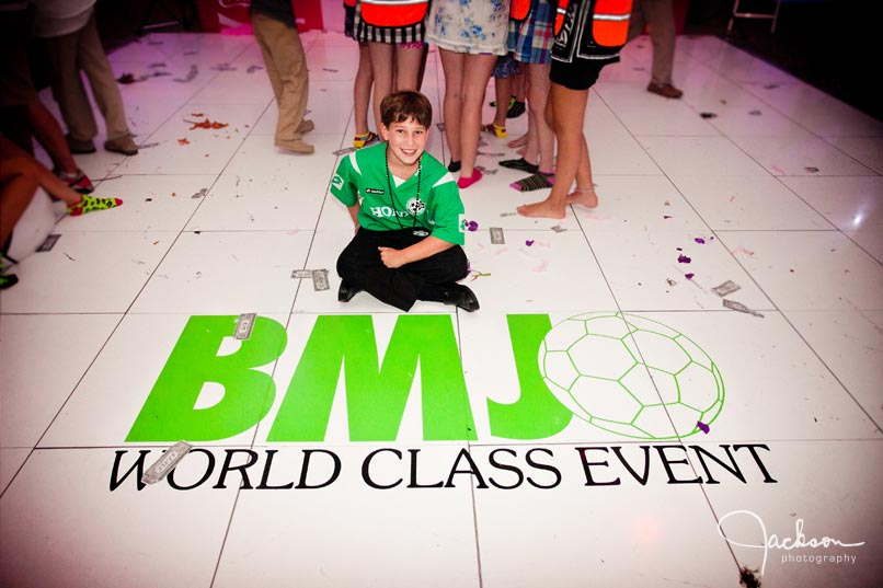 mitzvah boy on floor with green soccer graphic