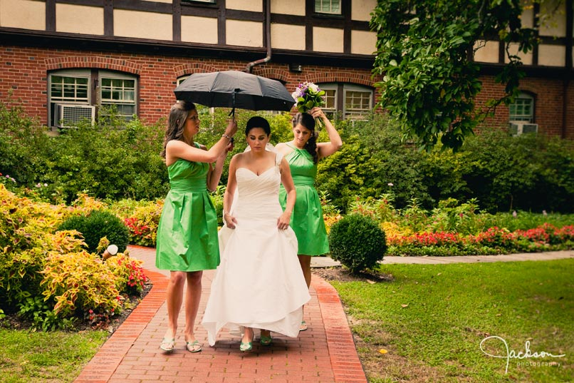 bride and bridesmaids under umbrella