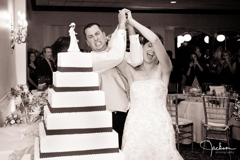 bride and groom cutting cake with firefighter axe