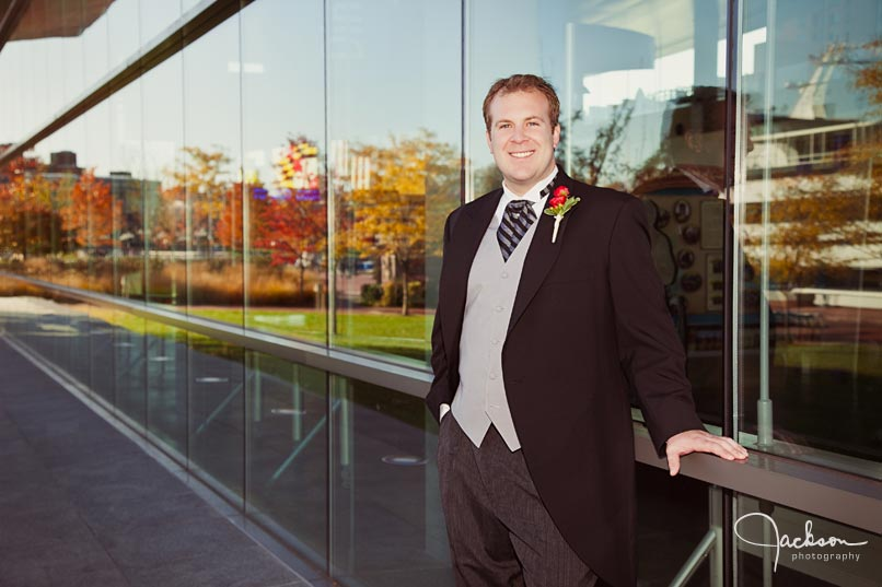 groom in front of reflective glass