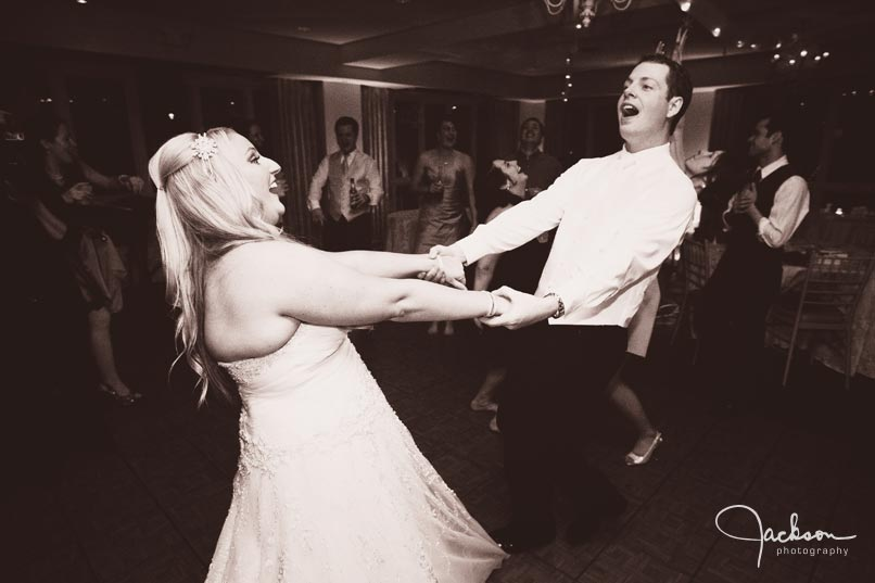 bride and groom swinging each other around