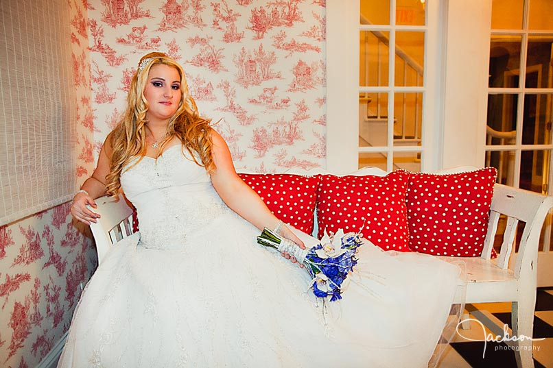 bride posing on red and white chair