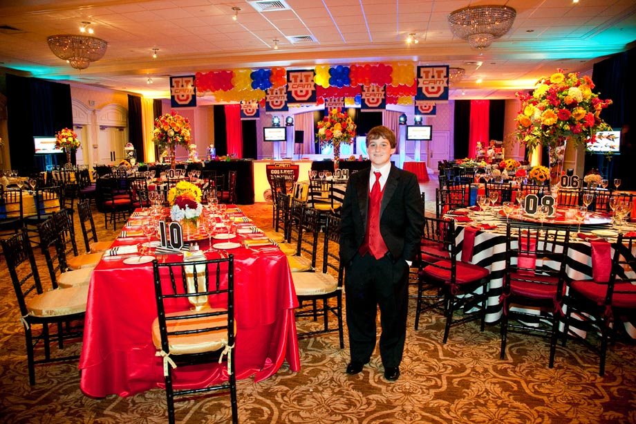 mitzvah boy in front of decorated tables