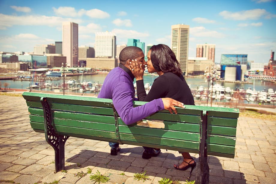 couple kissing on green park bench