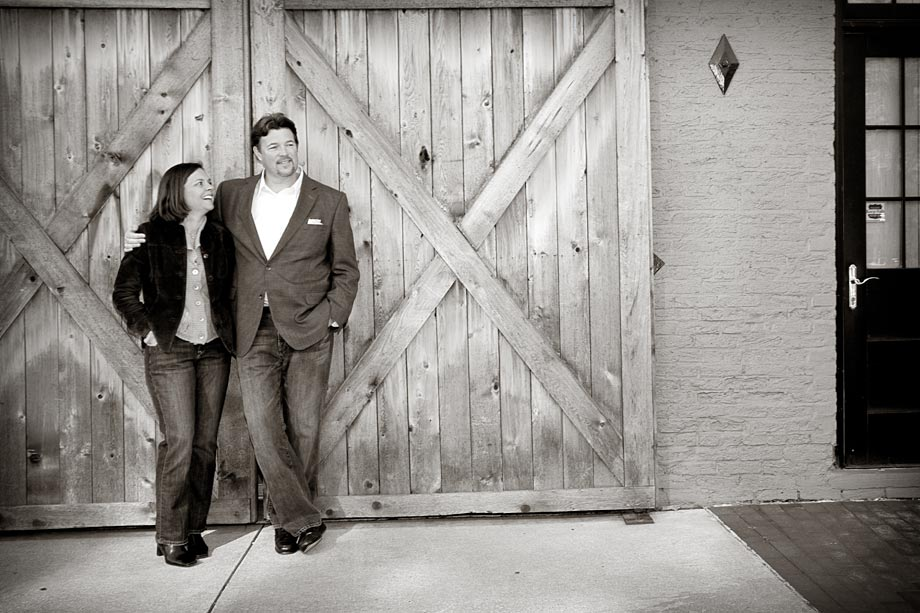 couple posing in front of large door
