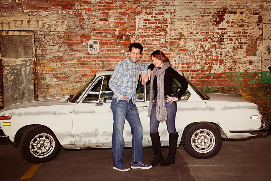 couple posing in front of old white car