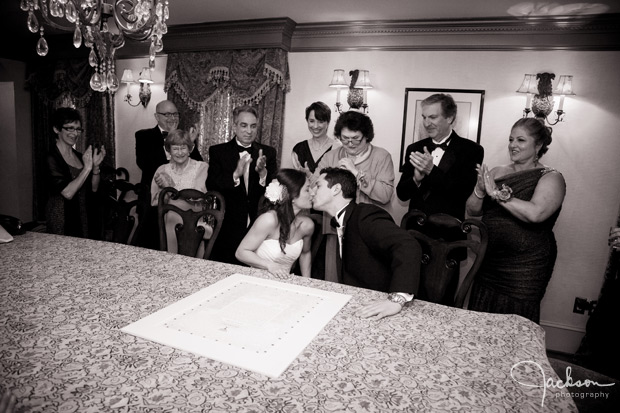 bride and groom kissing at ketubah signing