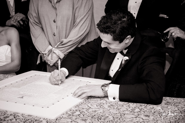 groom signing the ketubah
