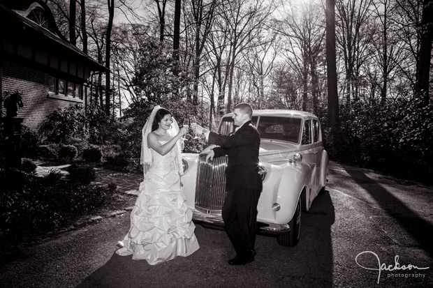 bride and groom toasting in front of rolls royce