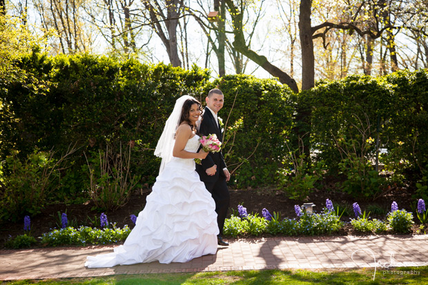 bride and groom walking down path by greenery
