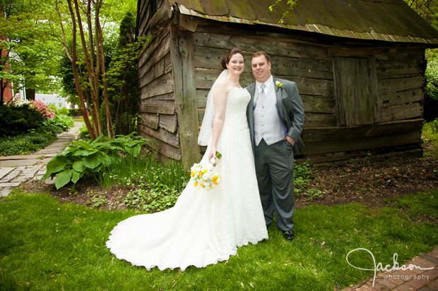 bride and groom posing in front of rustic shed
