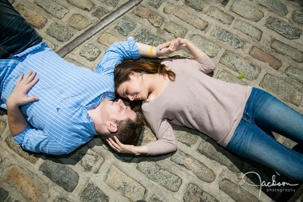 man and woman laying on cobblestone