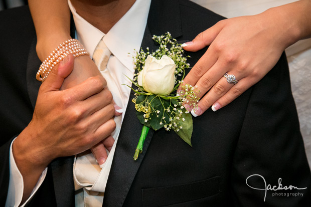 white rose boutonniere with hands and rings