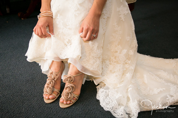 bride showing brown flowered lace shoes