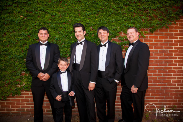 groom and groomsmen in front of ivy brick wall