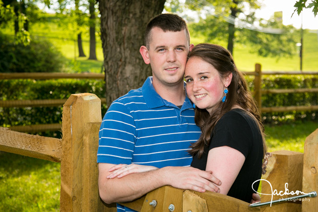 couple leaning on wooden fence