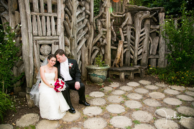 bride and groom sitting on tree stump at AVAM garden