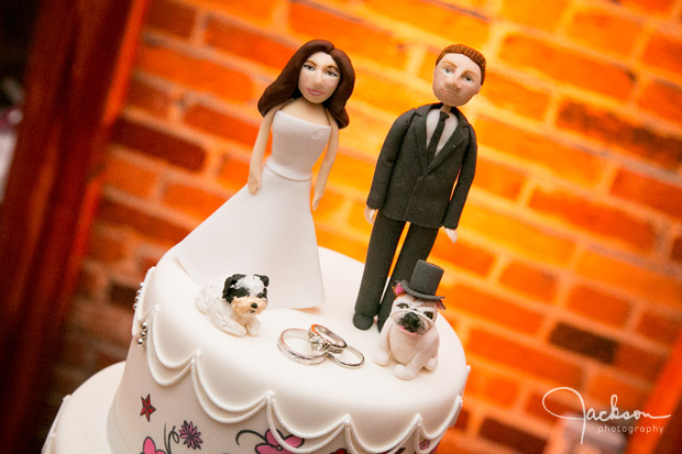 cartoonish cake topper of bride and groom with dogs