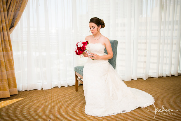 bride sitting in blue chair with red and white bouquet