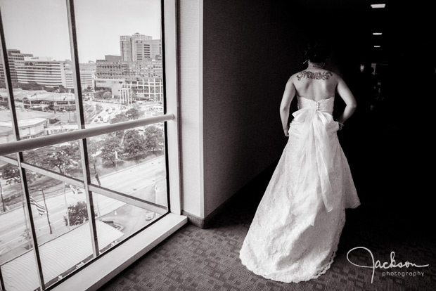 bride walking down hotel hallway with window light