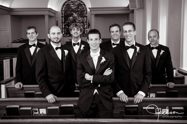 groom and groomsmen amongst church pews