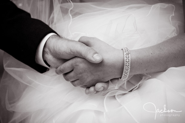 couple holding hands with ornate bracelet