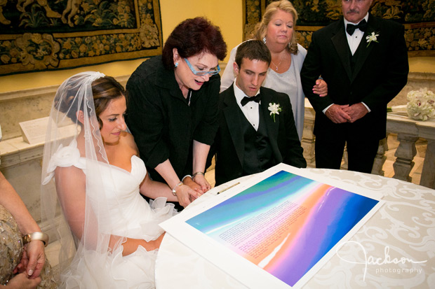 couple signing brightly colored ketubah