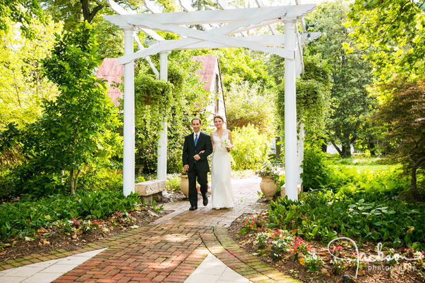 bride and groom walking beneath garden canopy