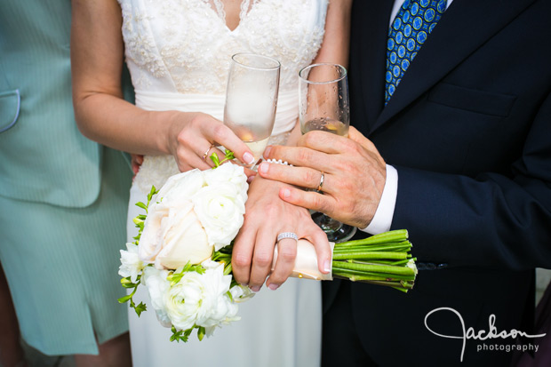 bride and groom's hands with rings and flowers