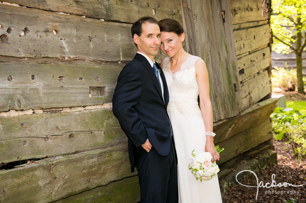 bride and groom leaning on grey barn
