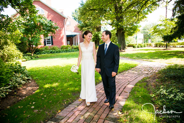 bride and groom walking along brick path