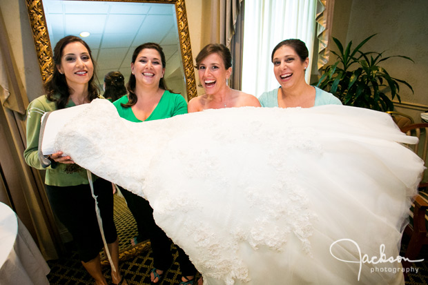 Bride and bridesmaids holding the bridal gown