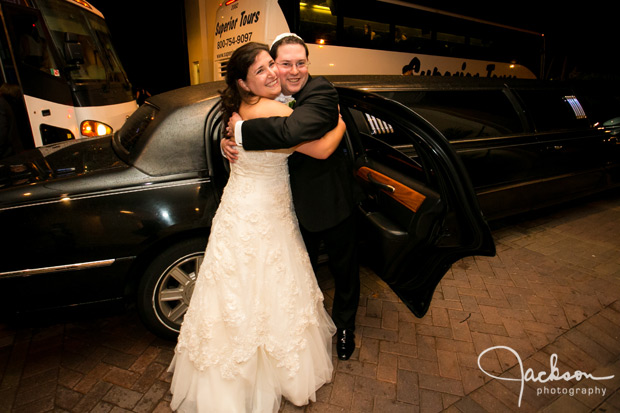 bride and groom hugging in front of limo