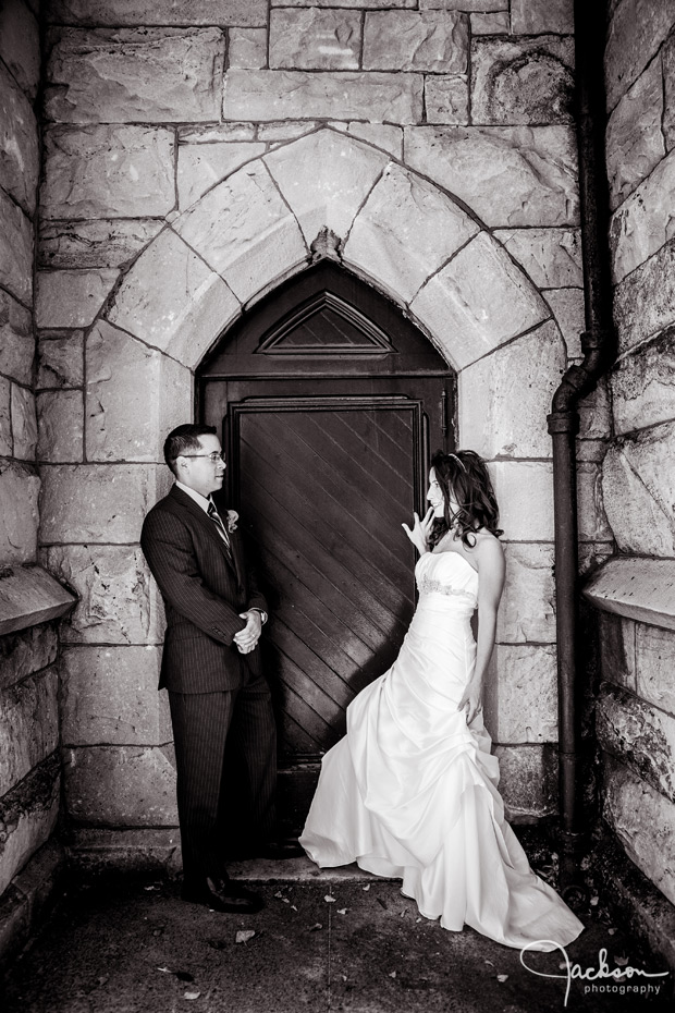 bride and groom by grungy stone wall and door