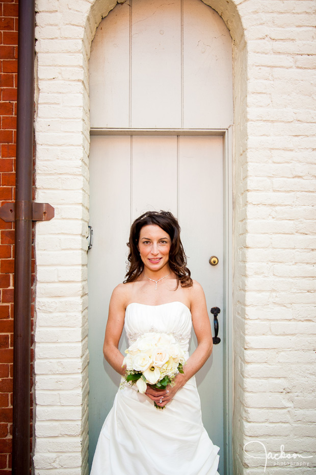 bride in small white brick archway