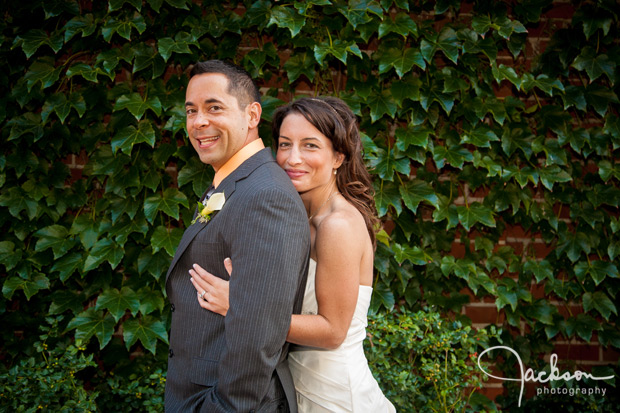 wedding couple hugging and laughing by ivy wall