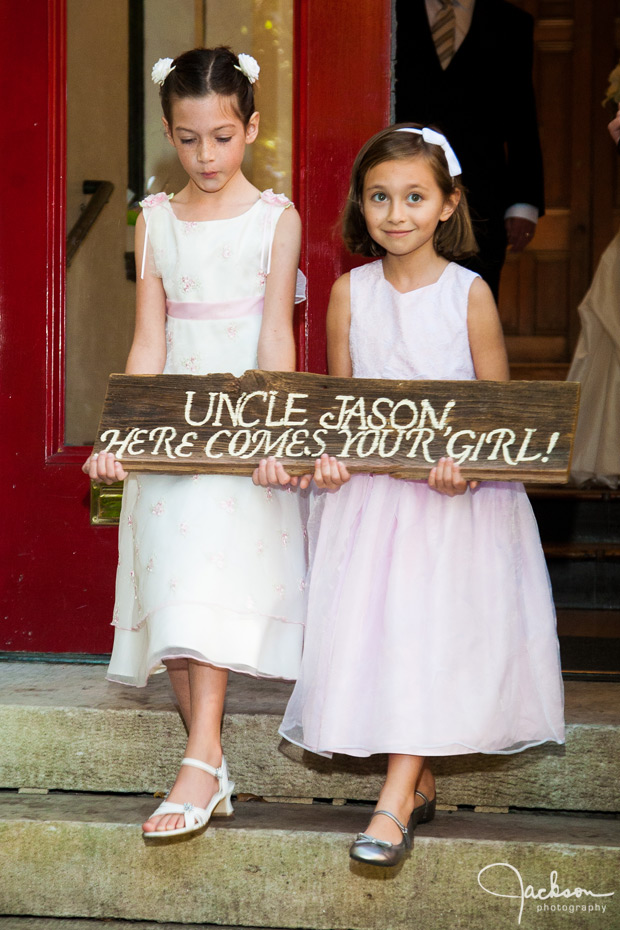 flower girls holding wooden sign