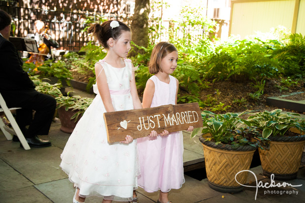 flower girls leaving with wooden sign