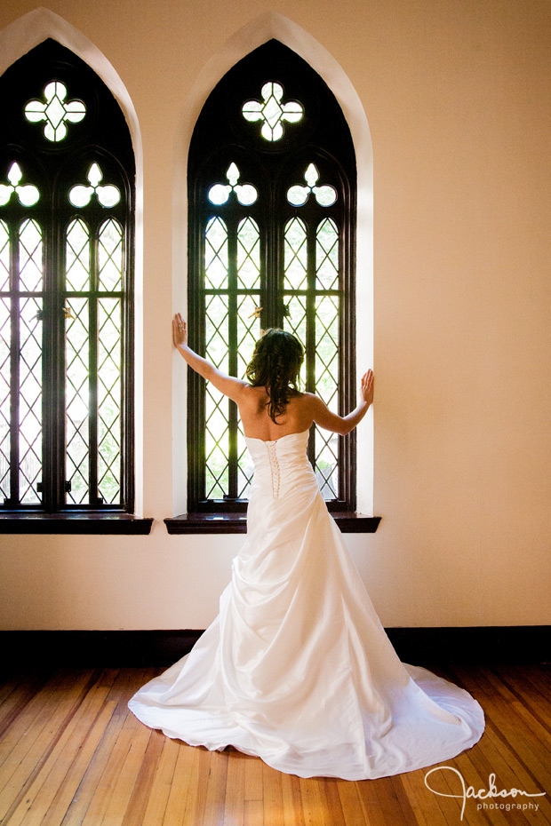 bride in dramatic pose by window