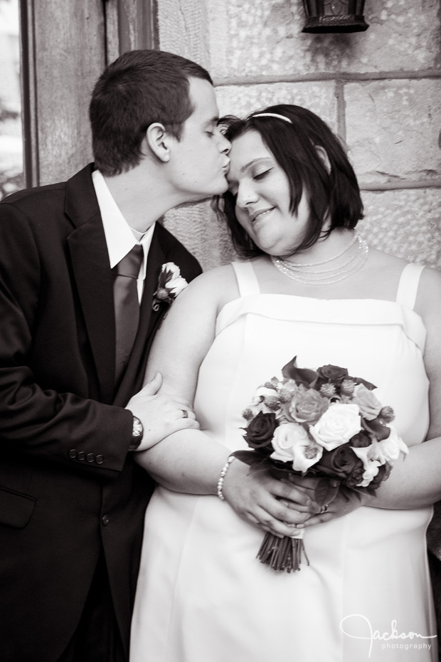 groom kissing bride black and white photography