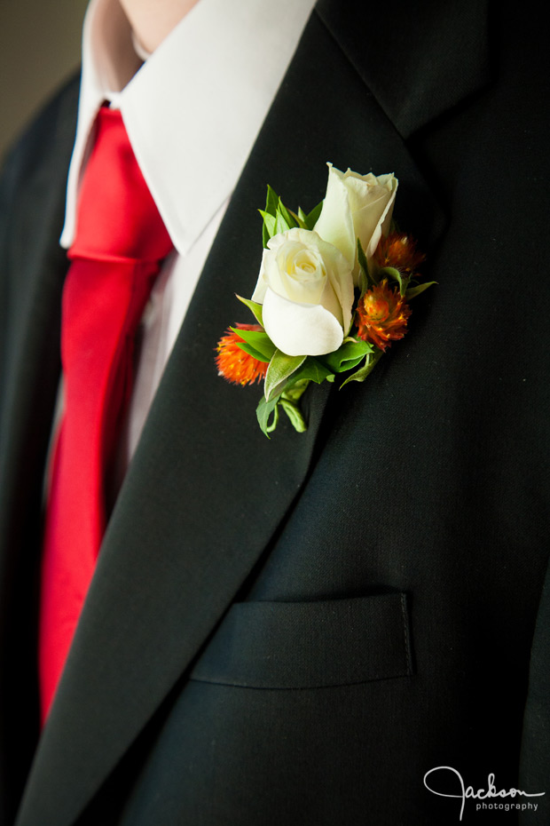 red tie ivory rose boutonniere