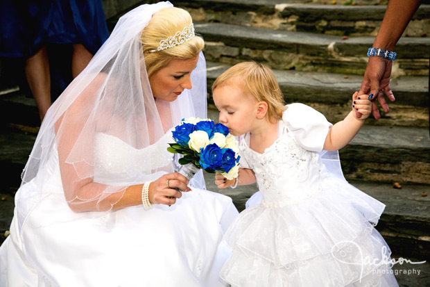bride letting flower girl smell bouquet